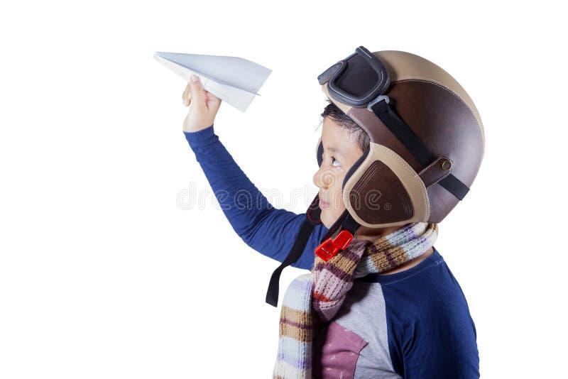 De leuke jongen speelt een document vliegtuig stock fotografie