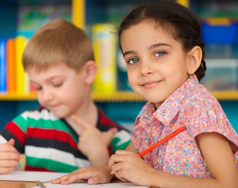 De leuke kinderen bestuderen bij opvang stock afbeeldingen