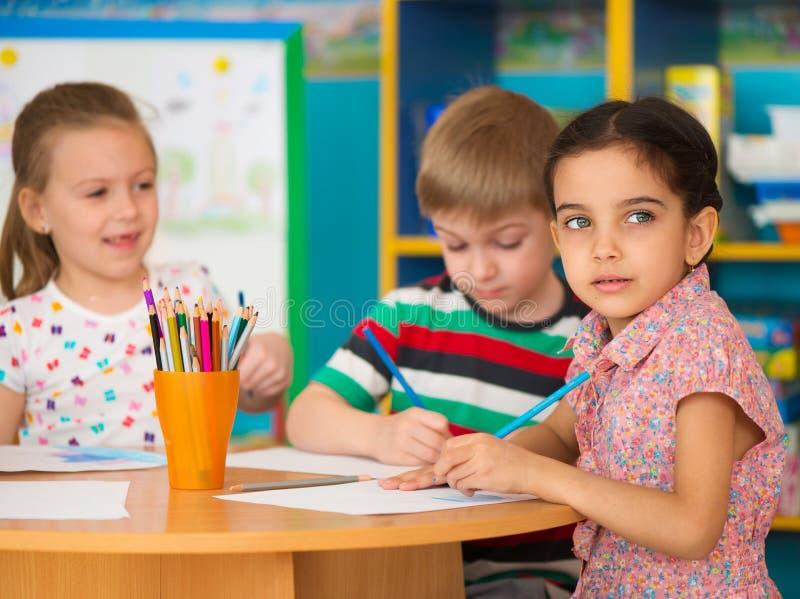 De leuke kinderen bestuderen bij opvang royalty-vrije stock afbeeldingen