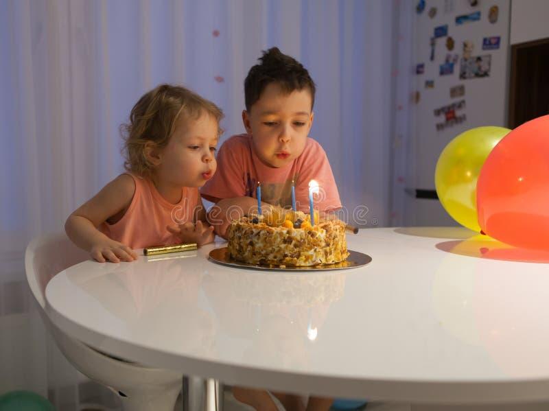 De leuke kleine broers die uit schouwt op verjaardagscake bij partij blazen stock afbeeldingen