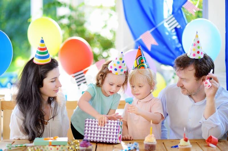 De leuke kleine kinderentweelingen en hun ouders die pret hebben en vieren verjaardagspartij met kleurrijke decoratie en cake royalty-vrije stock afbeelding