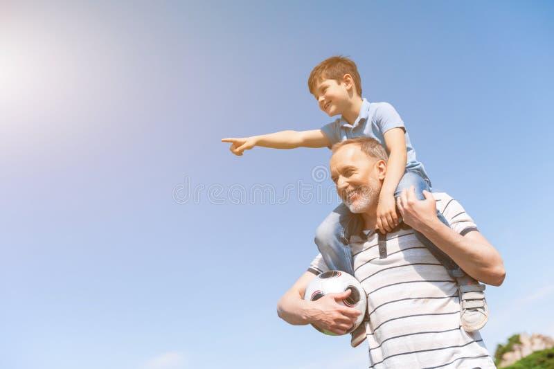 De leuke kleinzoon en de grootouder spelen in park stock afbeeldingen