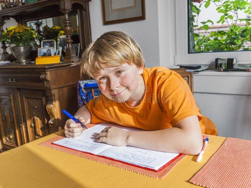 De leuke leerling schrijft in een boek en bereidt thuiswerk voor stock afbeelding