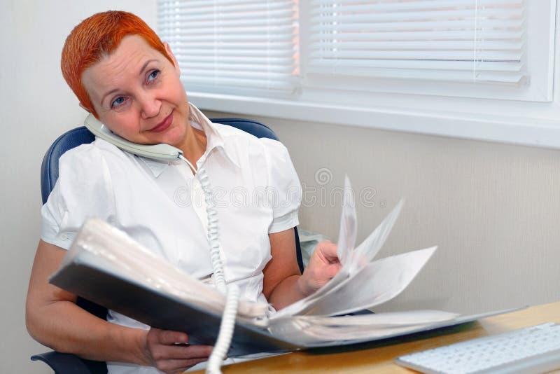 De leuke Manager die van het meisjesbureau op de telefoon spreken Glimlachen in een goede stemming stock fotografie