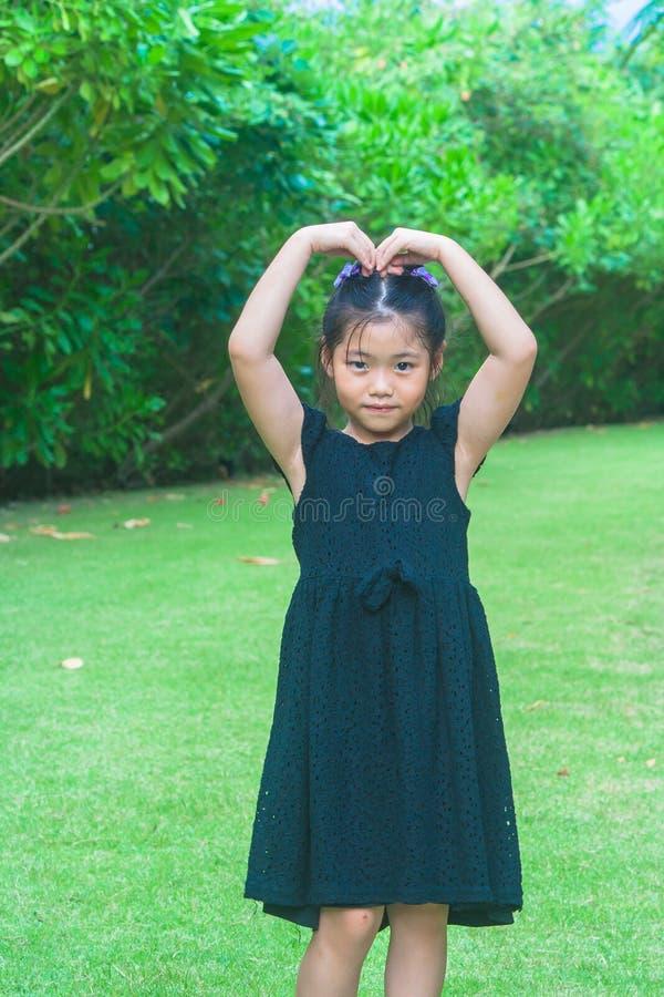 De leuke meisje status op groen gras en heft op van haar hand op om hart te maken overheadkosten met zonlichtachtergrond gestalte stock fotografie