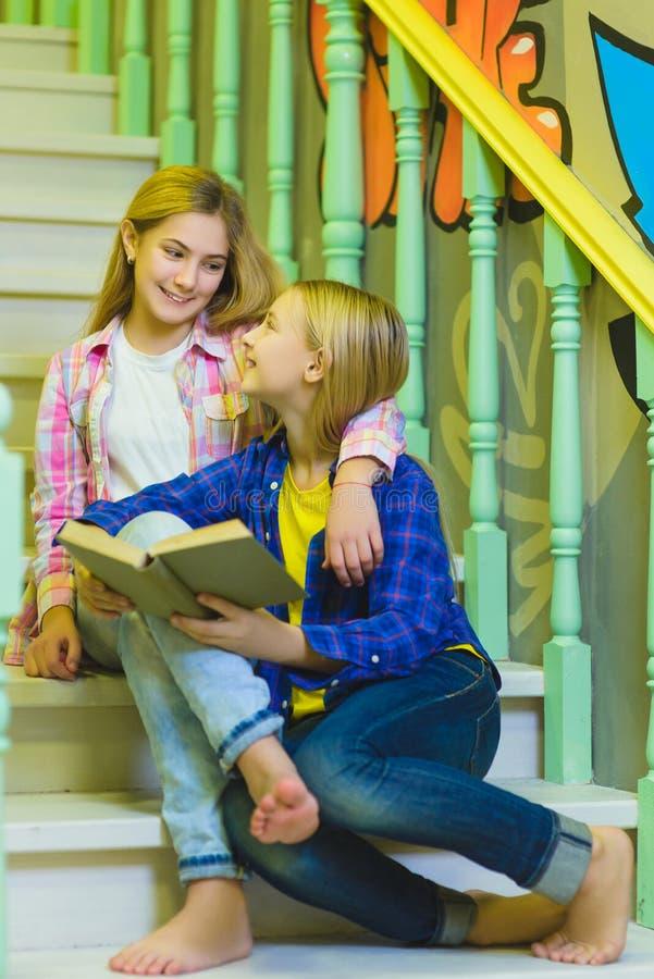 De leuke meisjes met holding boeken en zitting op treden van ladder binnen stock afbeeldingen