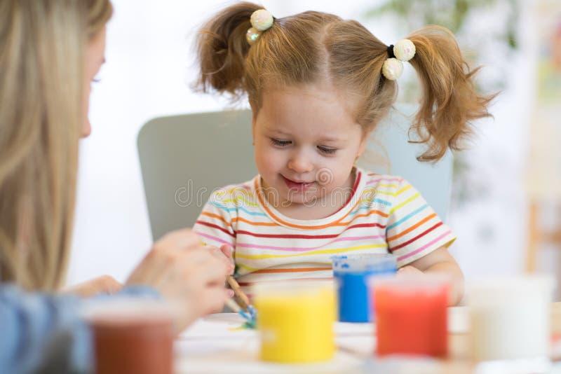 De leuke moeder onderwijst haar dochterjong geitje om te schilderen royalty-vrije stock foto