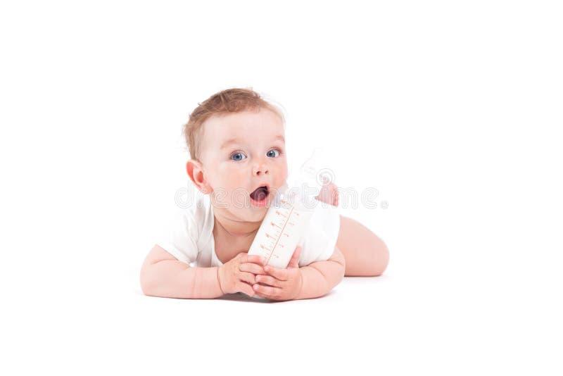 De leuke mooie babyjongen in wit overhemd ligt op buik met melk bott stock foto