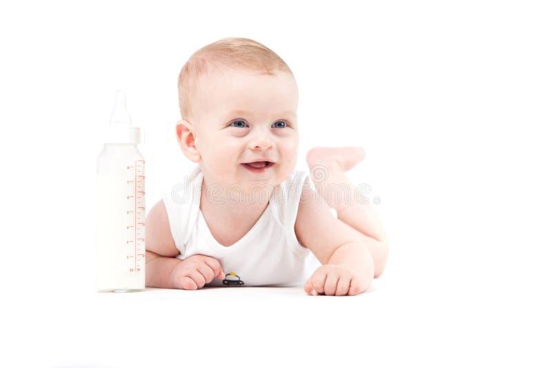 De leuke mooie babyjongen in wit overhemd ligt op buik met melk bott royalty-vrije stock foto