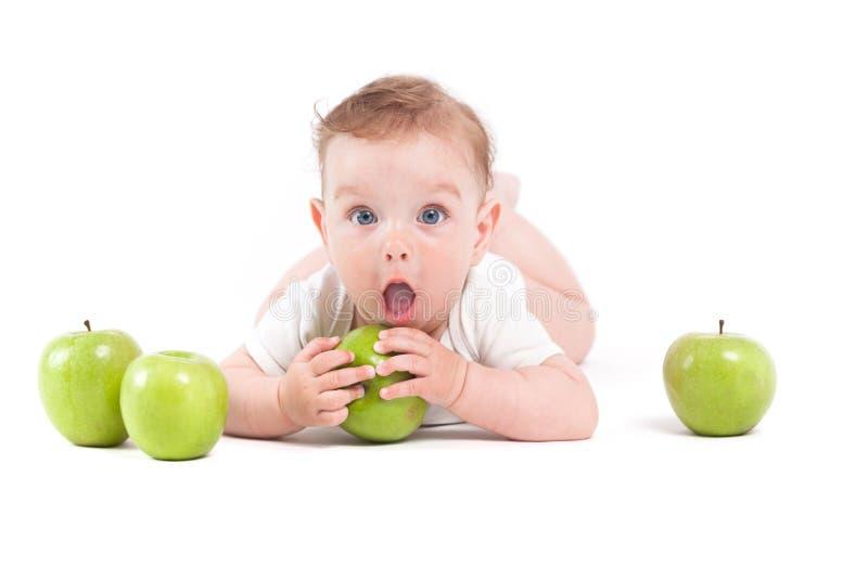 De leuke mooie babyjongen in wit overhemd ligt op groene buik en greep stock afbeelding