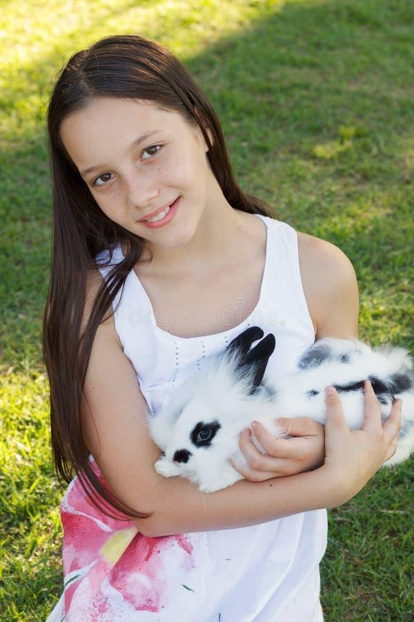 De leuke mooie glimlachende holding van het tienermeisje bij wit-zwart konijn stock foto's