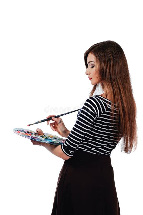 De leuke mooie meisjeskunstenaar die een palet en een borstel in het proces houden trekt inspiratie Witte geïsoleerde achtergrond stock foto's