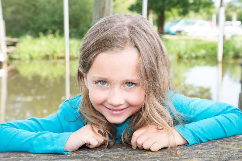 de leuke openluchtrivieroever van het kindmeisje in de zomer stock foto