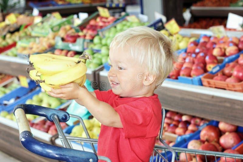 De leuke peuterjongen houdt bananen in zijn handen terwijl het zitten in boodschappenwagentje binnen supermarkt stock afbeeldingen
