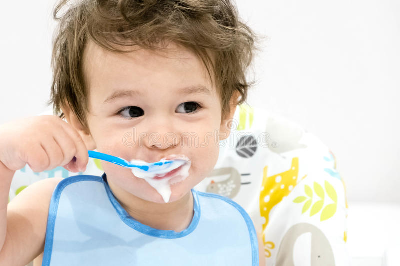 De leuke peuterjongen met blauwe lepel is yoghurt De kindglimlachen grappig jong geitje in een babyzetel mooie 2 éénjarigen weini stock foto