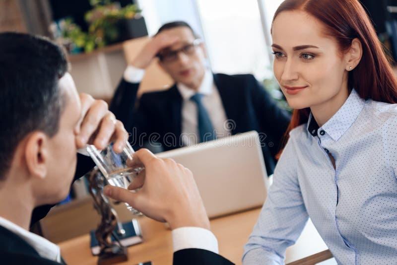 De leuke roodharige vrouw bekijkt mens, die glas water in advocaat` s bureau de drinken voor scheiding stock afbeelding