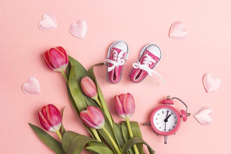 De leuke roze tennisschoenen van het babymeisje met tulup bloeit en wekker op een roze achtergrond stock afbeelding
