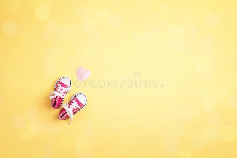 De leuke roze tennisschoenen van het babymeisje op gele achtergrond met exemplaarruimte royalty-vrije stock foto