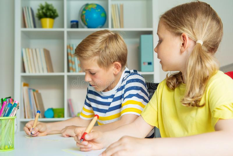 De leuke schoolkinderen zijn kwamen terug aan school en het leren bij de lijst in klaslokaal stock foto's