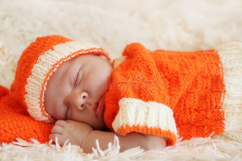 De leuke slaap pasgeboren baby kleedde zich in een gebreid oranje kostuum o royalty-vrije stock afbeelding