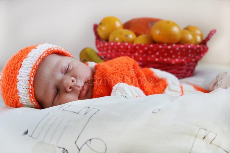 De leuke slaap pasgeboren baby kleedde zich in een gebreid oranje kostuum w stock afbeelding