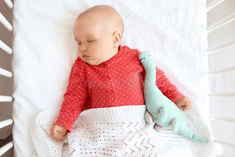 De leuke slaap van het babymeisje in voederbak stock foto's