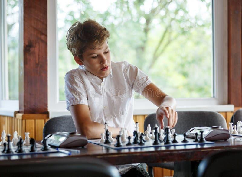 De leuke, slimme, jonge jongen in wit overhemd speelt schaak op het schaakbord in het klaslokaal Onderwijs, hobby, opleiding stock foto