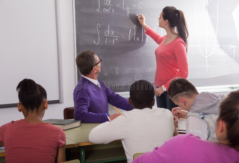 De leuke student lost taak dichtbij bord in klaslokaalwiskunde op royalty-vrije stock afbeelding
