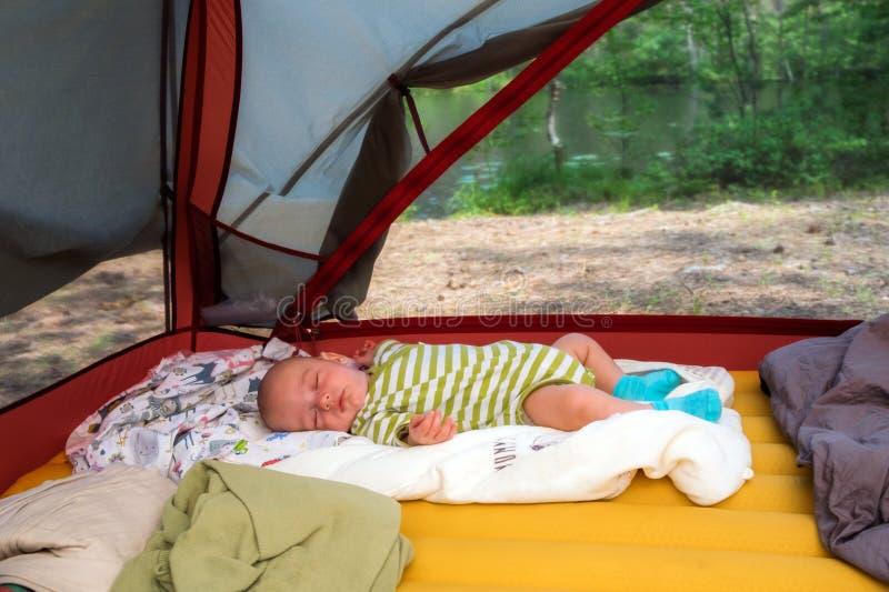 De leuke toerist van de babyjongen slaapt in openlucht in een tent in de zomertijd royalty-vrije stock afbeelding