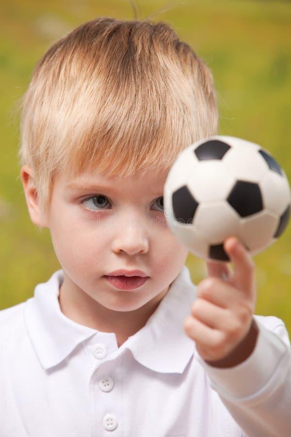 De leuke voetbal van de jongensholding in openlucht royalty-vrije stock foto