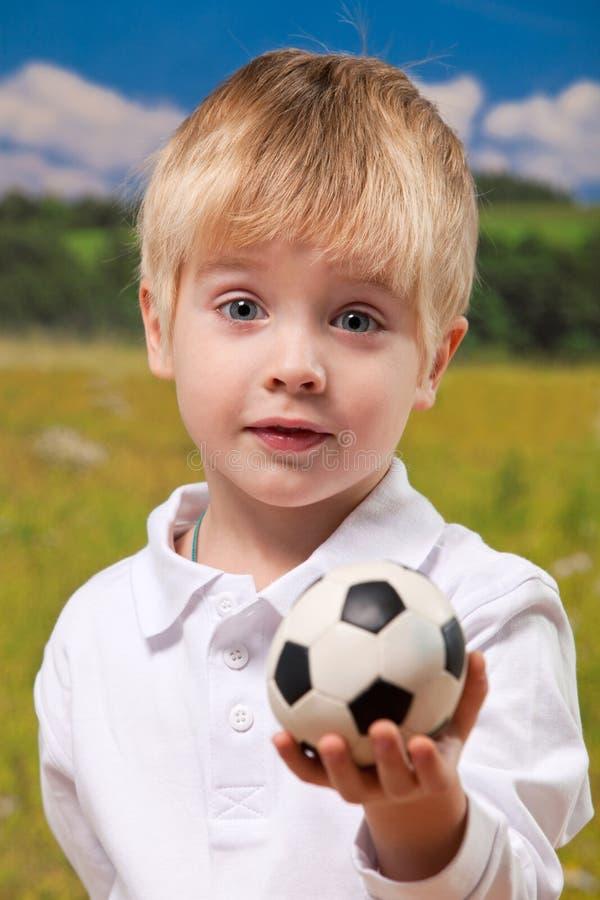 De leuke voetbal van de jongensholding in openlucht royalty-vrije stock afbeelding