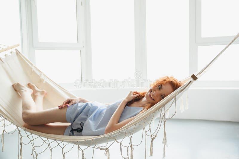 De leuke vrolijke jonge roodharigedame ligt op hangmat royalty-vrije stock foto