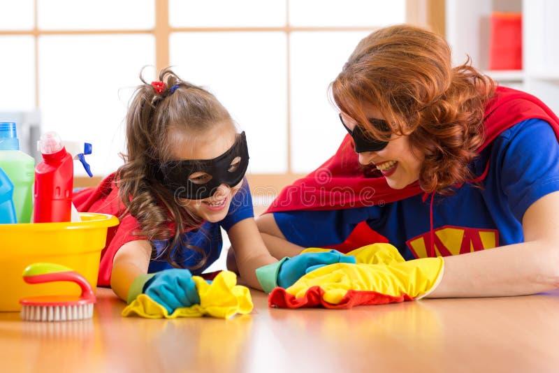 De leuke vrouw en haar jong geitjedochter kleedden zich als superheroes die de vloer en het glimlachen schoonmaken stock afbeeldingen