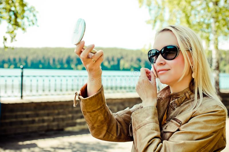 De leuke vrouw kijkt in kleine spiegel op de straat en verbetert omhoog maakt Vage natuurlijke achtergrond royalty-vrije stock foto's