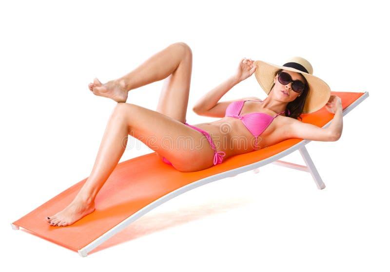 De leuke vrouw op sinaasappel sunbed stock afbeelding
