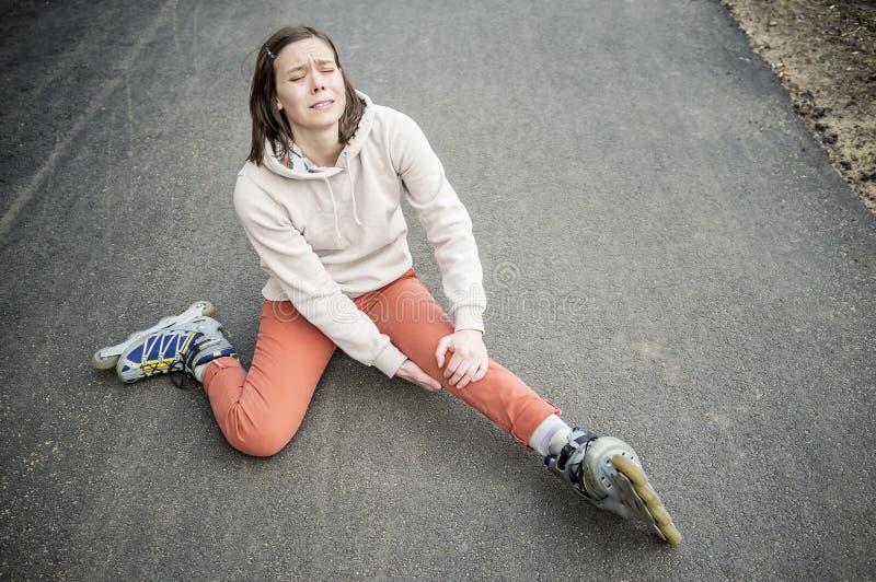 De leuke vrouw viel berijdend op rolschaatsen stock foto's