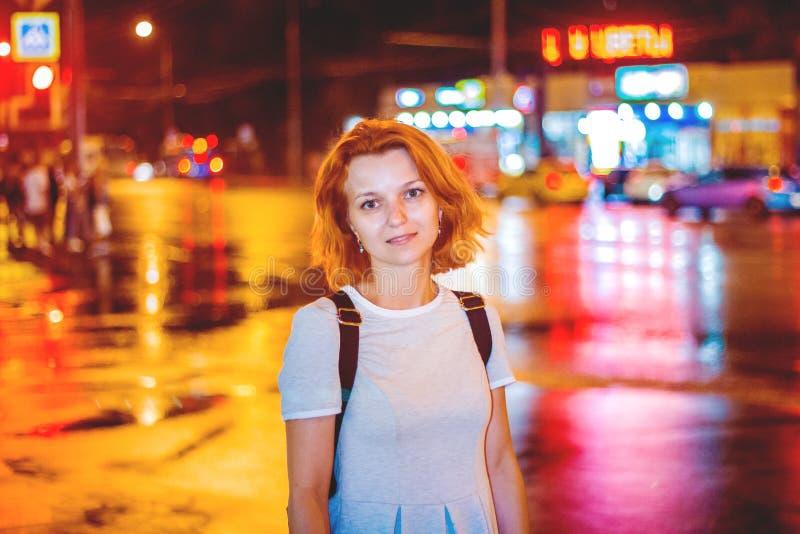 De leuke vurige roodharige meisje status in de nachtstad stak met lichten en koplampen aan die auto's overgaan royalty-vrije stock fotografie