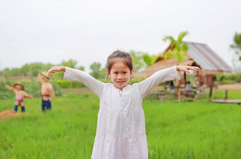 De leuke wapens van weinig Aziatische meisjesrek bij de verse groene padiegebieden royalty-vrije stock fotografie