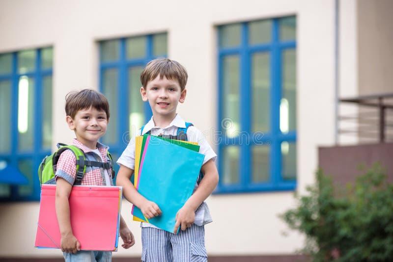 De leuke weinig schoolstudenten spreken levendig op het schoolplein Chil stock afbeeldingen