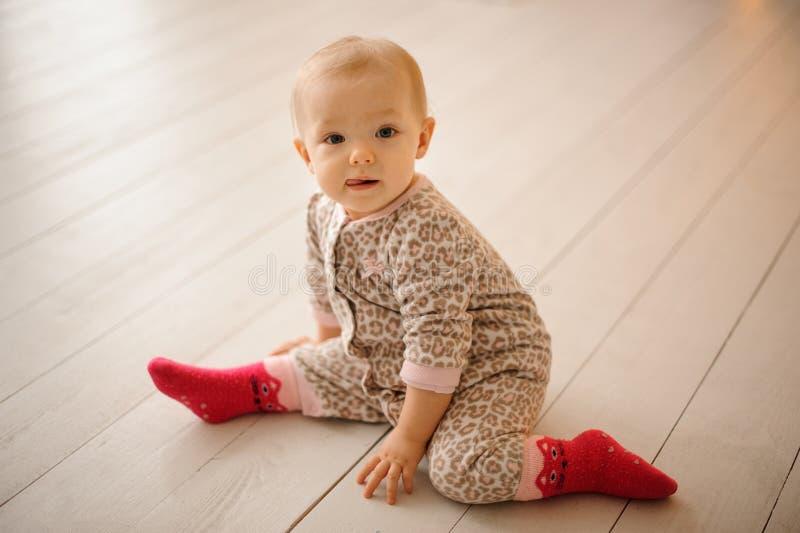 De leuke zitting van het babymeisje alleen op de vloer stock afbeelding