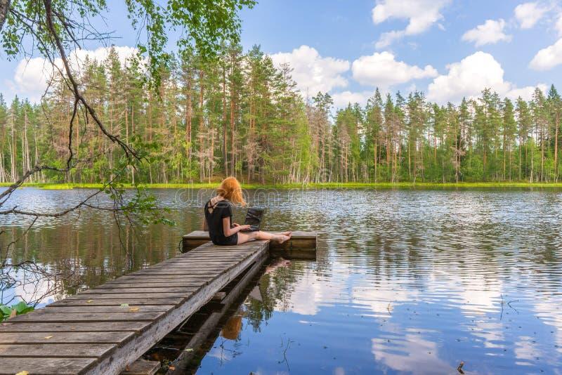 De leuke zitting van het gembermeisje op houten planked voetpad en het werken met laptop in de zomerdag tegen mooi landschap van  stock afbeelding