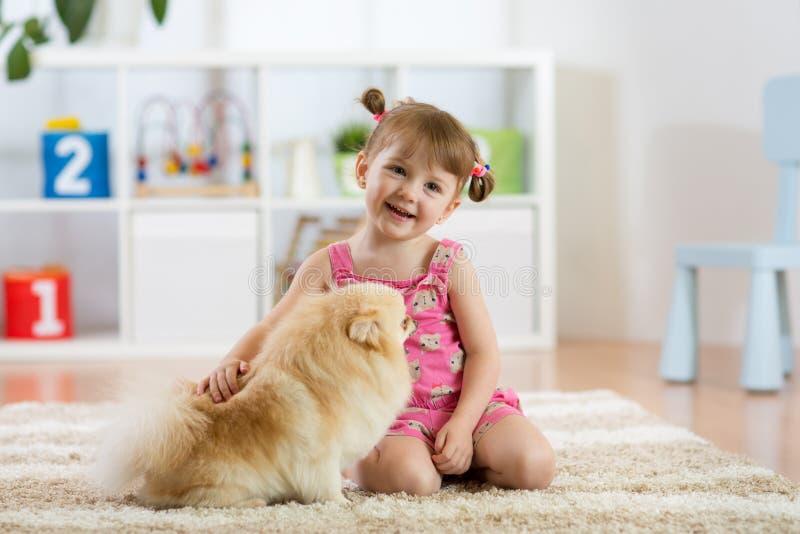 De leuke zitting van het kindmeisje op de vloer met haar hond stock afbeelding