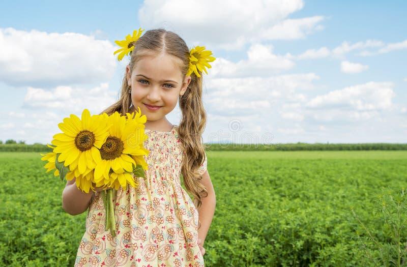 De leuke Zonnebloemen die van de meisjeholding, die in aard genieten van en op zomer lachen stock afbeeldingen