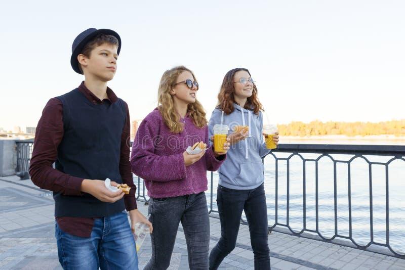 De levensstijl van adolescenten, de jongen en twee tienermeisjes lopen in de stad Lachen, sprekende kinderen die straatvoedsel et royalty-vrije stock foto