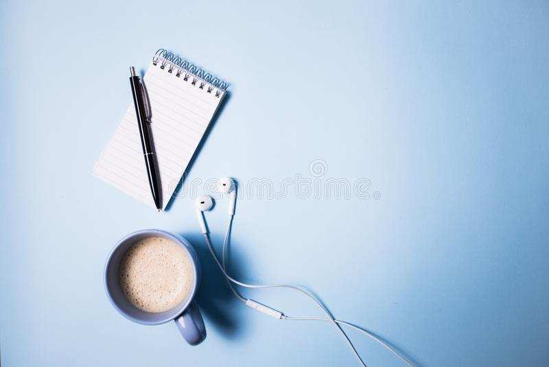 De levering van het bureau Hoogste mening over geopende notitieboekje, pen, hoofdtelefoon, laptop en kop van koffie op blauw stock afbeeldingen