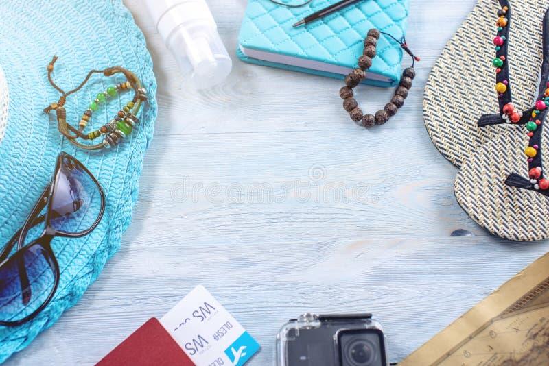 De levering van de reisvakantie: hoed, zonnebril, wipschakelaars, paspoort op blauwe achtergrond Het gaan op een reis naar het ov stock foto