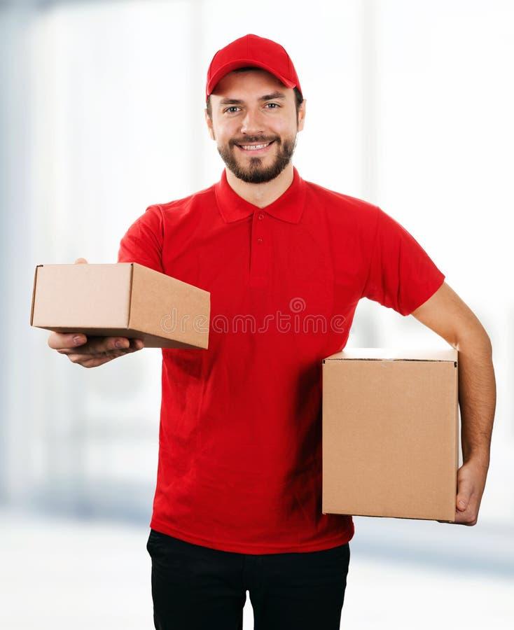 De leveringsdienst - jonge glimlachende bezorger met karton boxe stock foto