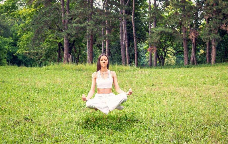 De levitatie van de yogameditatie - vrouwenconcentratie in yogaoefening stock foto