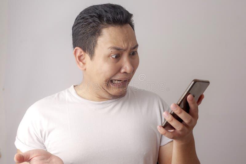 De Lezing die van jonge Mensentexting bij Zijn Telefoon het Droevige Schreeuwen babbelen royalty-vrije stock foto