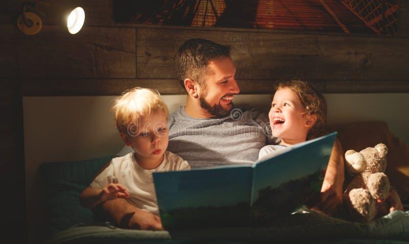 De lezing van de avondfamilie de vader leest kinderen boek vóór goin royalty-vrije stock afbeelding